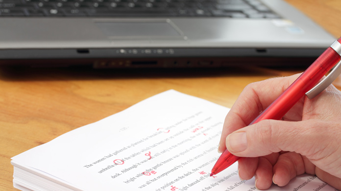 Hand holding a red pen making corrections to a printed document